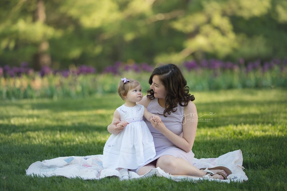 baby girl looks at mother during outdoor photo session with purple flowers in columbus ohio
