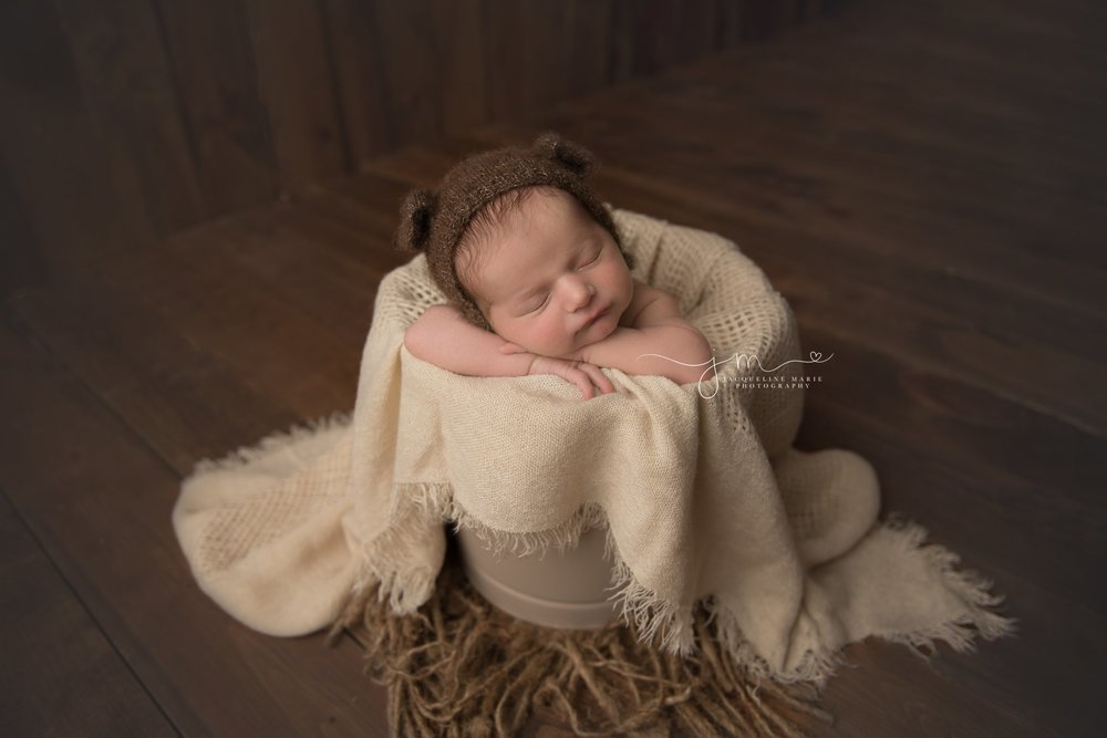 columbus ohio newborn baby boy wears teddy bear bonnet while posed in bucket for newborn session