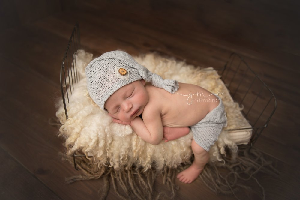 newborn baby boy wears hat and shorts while posed on baby bed in columbus ohio photography studio