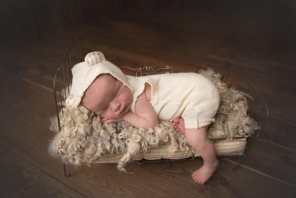 columbus ohio newborn photographer poses baby boy in cream teddy bear romper