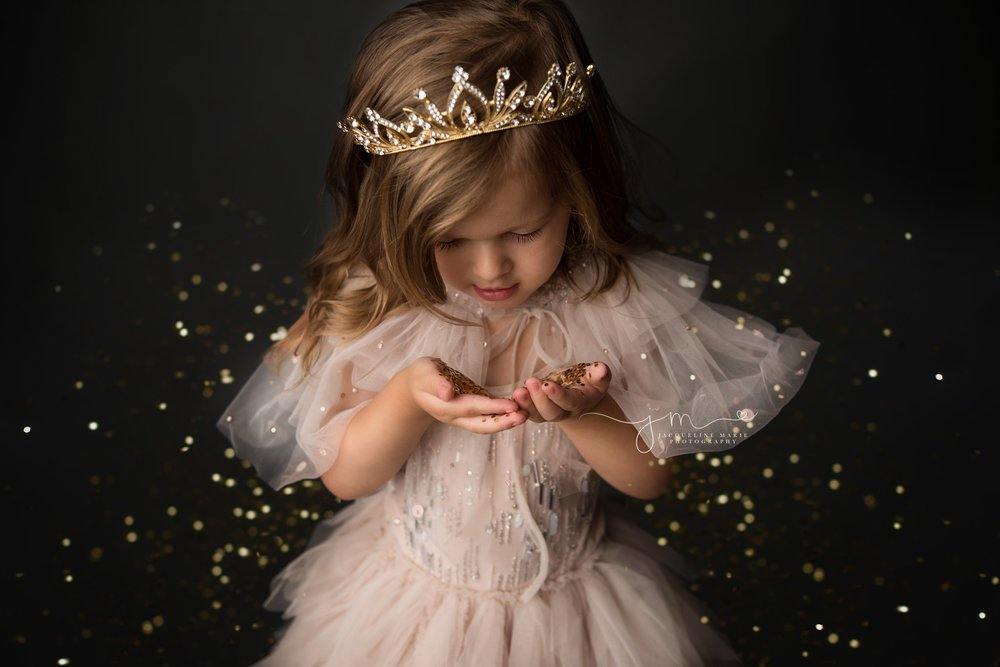 little girl blows gold glitter from her hands during glitter photography session in columbus ohio