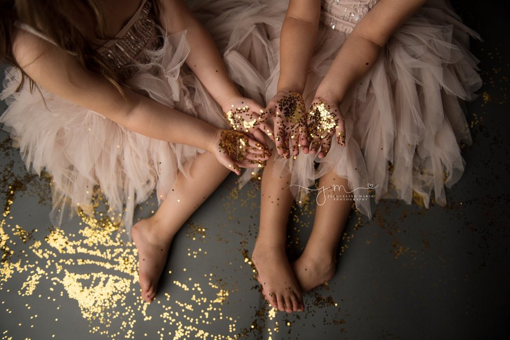 glitter photography session with twin sisters holding glitter in their hands