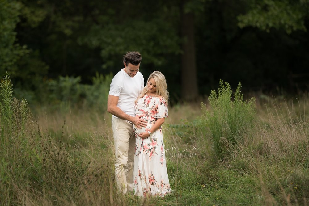 maternity photo session in Columbus ohio during sunset and mother wears floral gown