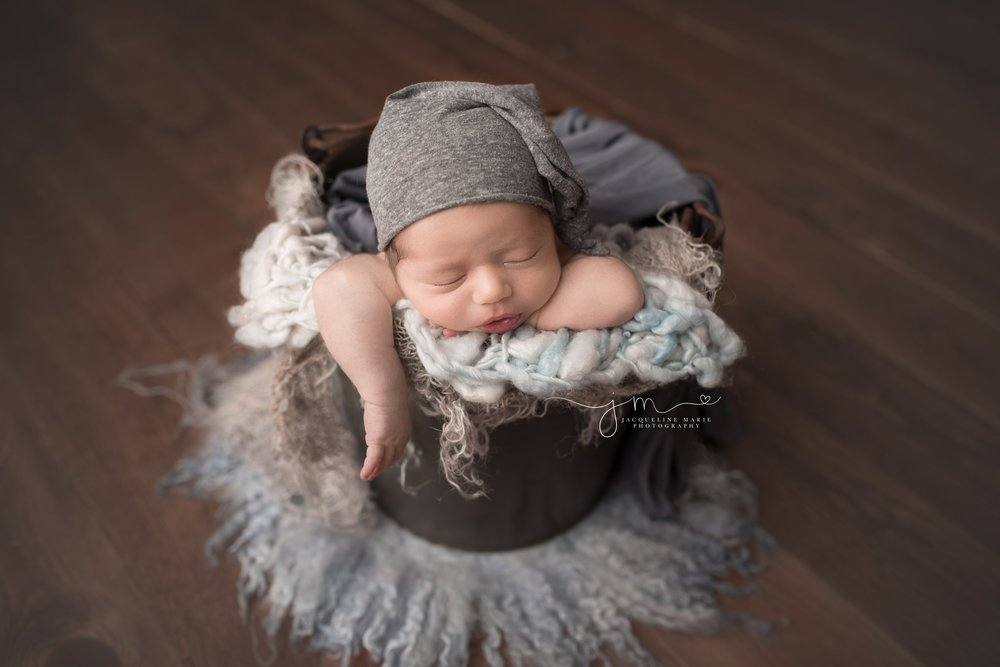 columbus ohio newborn bay boy wears gray sleepy hat while posed in bucket for newborn photography session