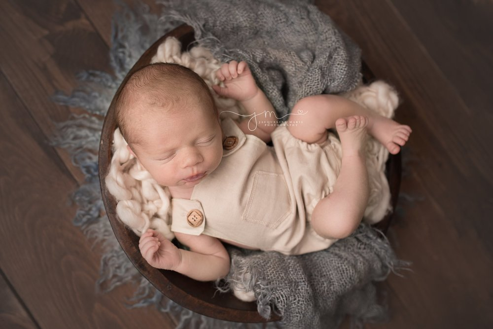 columbus ohio newborn baby boy wears cream overalls while posed in wood bowl for newborn photography session
