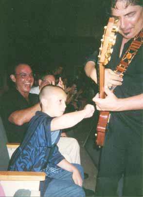 My son Justin strums Craig Chaquico's guitar King Center 2004