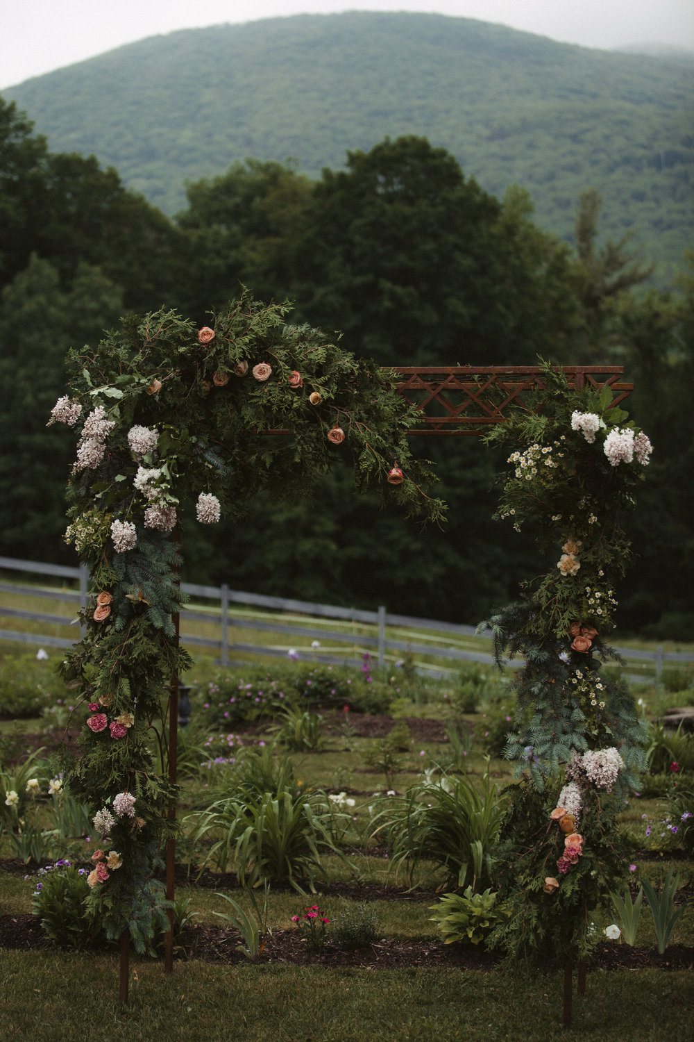 Ceremony flower arrangements by Nectar & Root | Wedding floral design services in Burlington, Vermont (VT) | Arbor with lilacs, garden roses, chamomile
