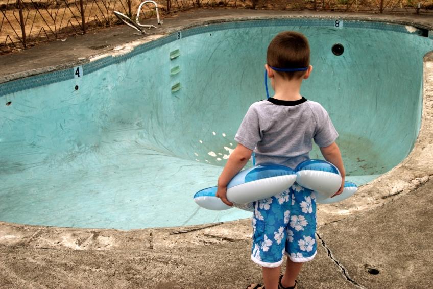 Boy Next to Empty Pool