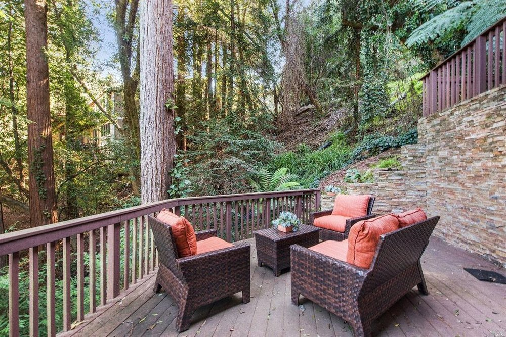 Ample deck & patio space with views of lush landscaped grounds.