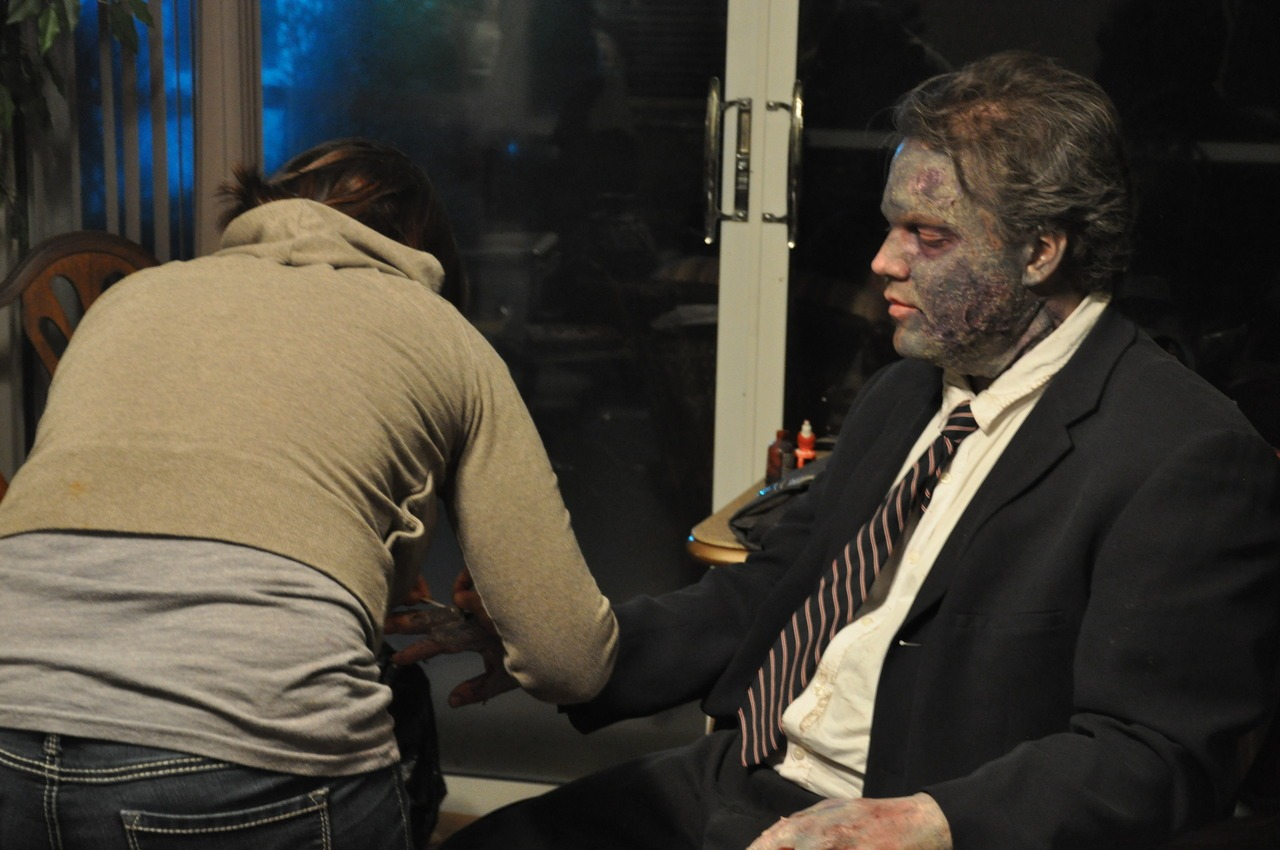 In today's behind the scenes photo, Joannie Atkins, doing double duty as our beauty make-up artist as well as handling most of our practical make-up effects, touches up our zombie, Chris Cline.   Photo by Shawn Bowen.