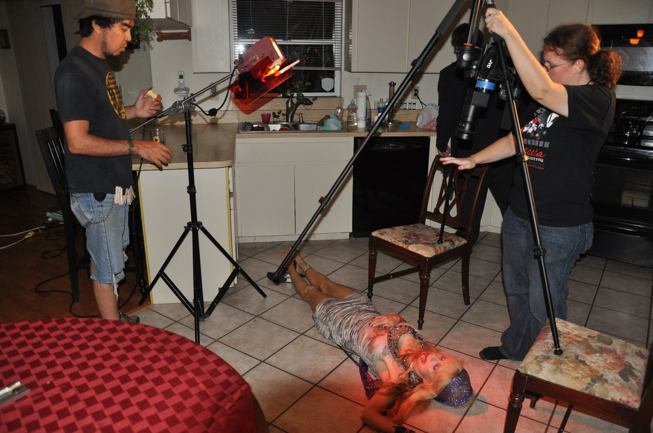 """In today's behind the scenes photo, we're setting up for the last shot you see in the trailer, when Stella Buio gets her come-uppance. From left: Wheat, Linnea Quigley, Chris Cline (with his back turned toward us), and myself (Lori Bowen). For those who might be wondering how I managed to mount my camera upside down on a tripod: this is a very lightweight, but also very flexible, photographic tripod from Vanguard's Alta Pro range. The middle post comes out very easily and you can reattach it from underneath. That middle post also """"cranes"""" 180 degrees (I haven't used that yet, but it was one of the things that made me even more excited about getting this tripod.) I have a ball mount head on it for even greater flexibility of how I position the camera. Click here to see the trailer. Photo by Shawn Bowen."""