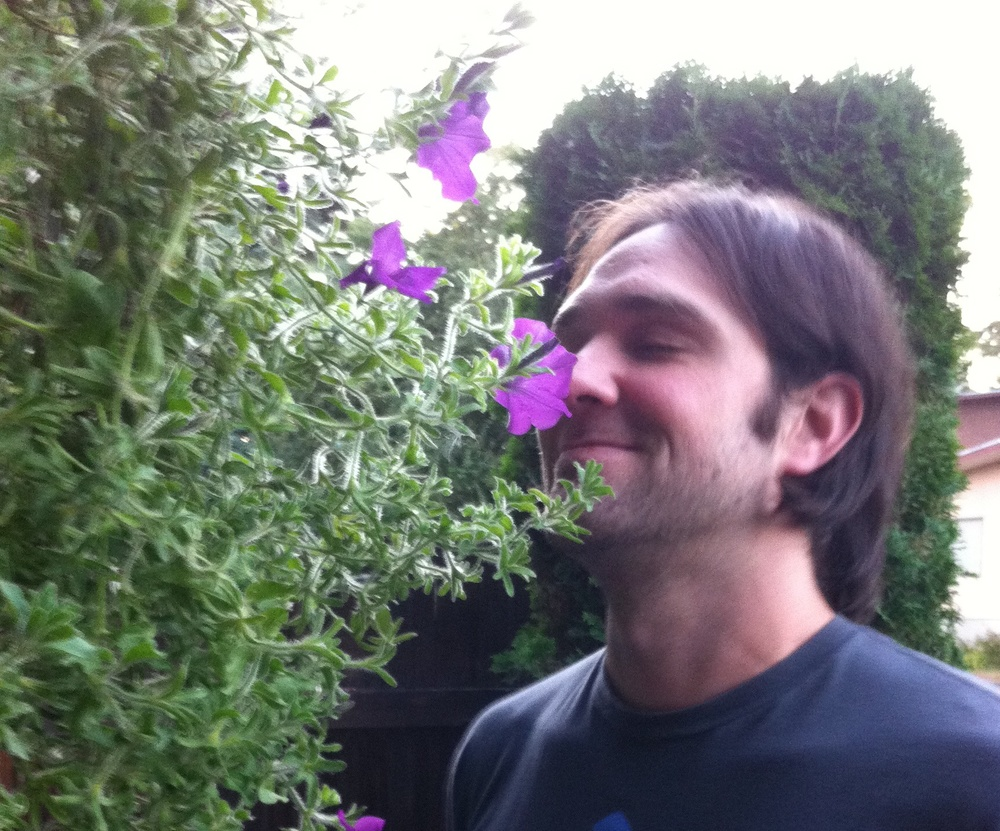 Benny takes time to smell a purple petunia. 4 September 2011.