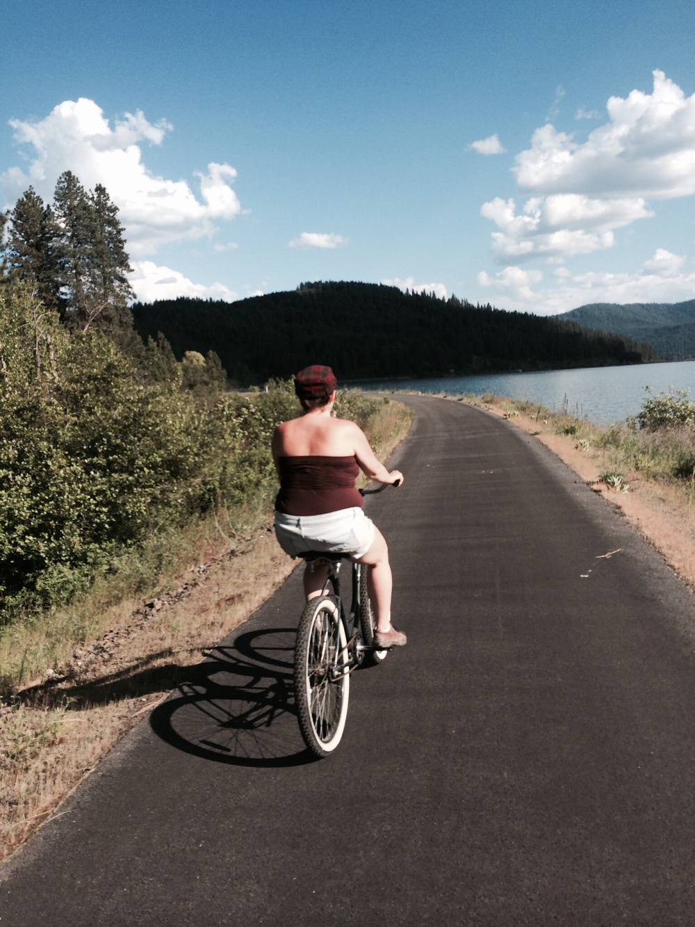 "Jill riding her vintage Schwinn cruiser on the ""rails to trails"" path along Lake Chatcolet.  1 June 2014."