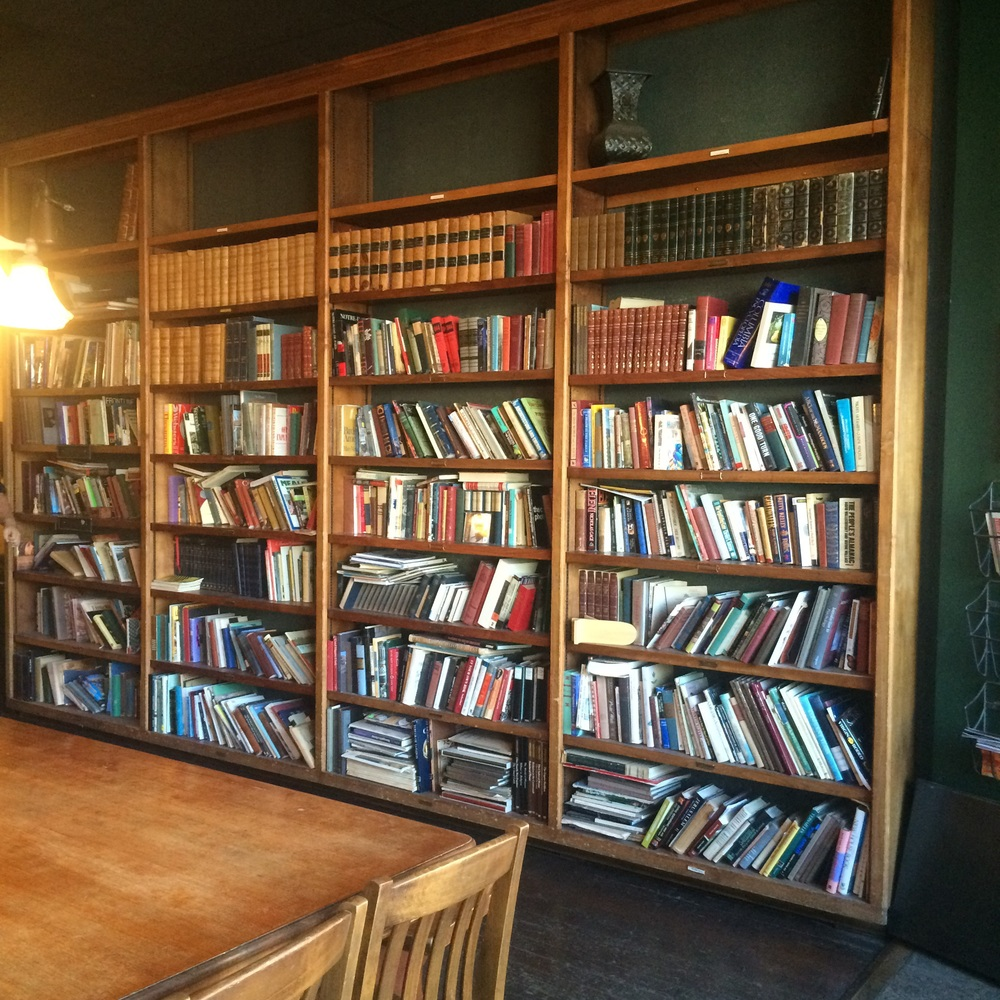 A collection of books, their spines zig-zagging.  Leaning on each other.  Bucer's Coffee House, Moscow, Idaho.
