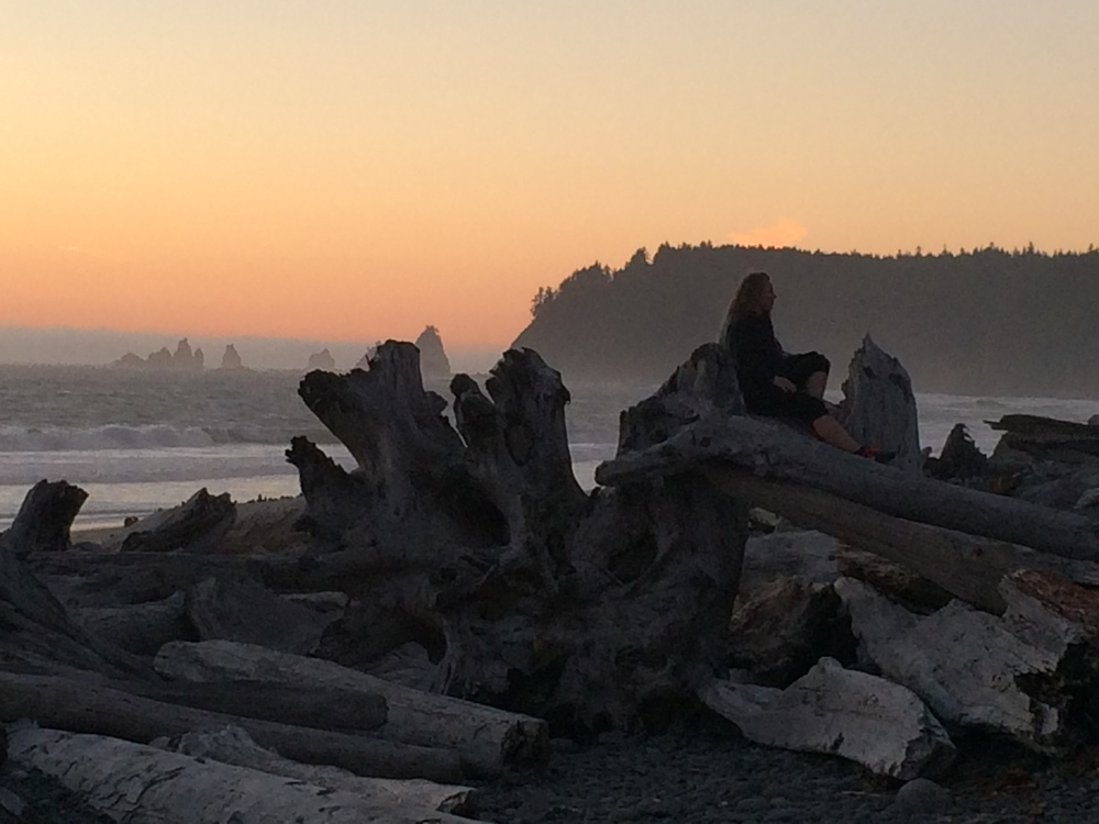 A woman rests upon a stack of driftwood during sunset at Ruby Beach in Olympic National Park.  August 2014.