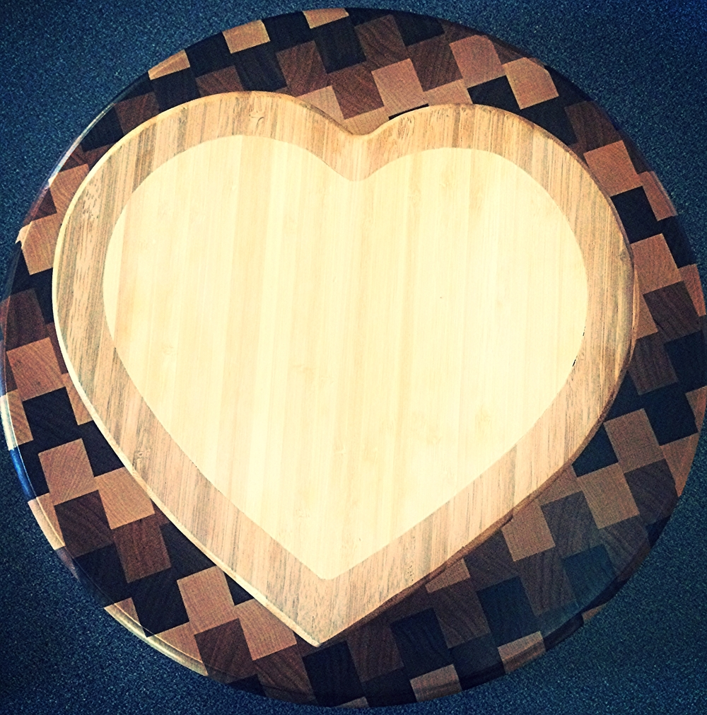 Heart shaped cutting board lays atop circle cutting board made by Ryan Curtis.