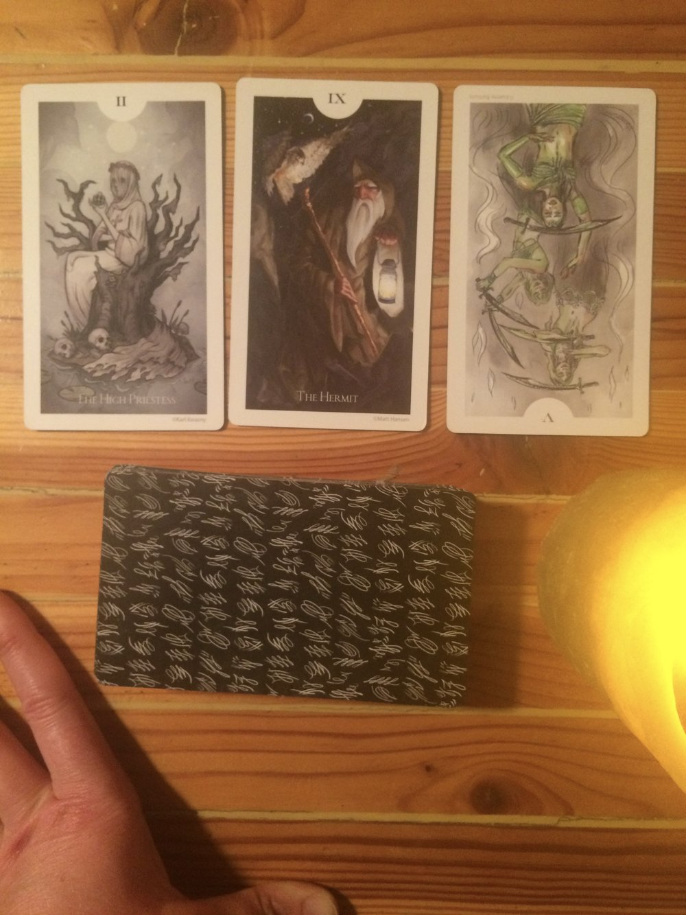 A three-card spread on the new moon using The Light Grey Tarot.   The High Priestess, The Hermit, and the Five of Swords (reversed).