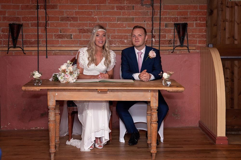 Bride and groom signing registry Donington park farmhouse hotel