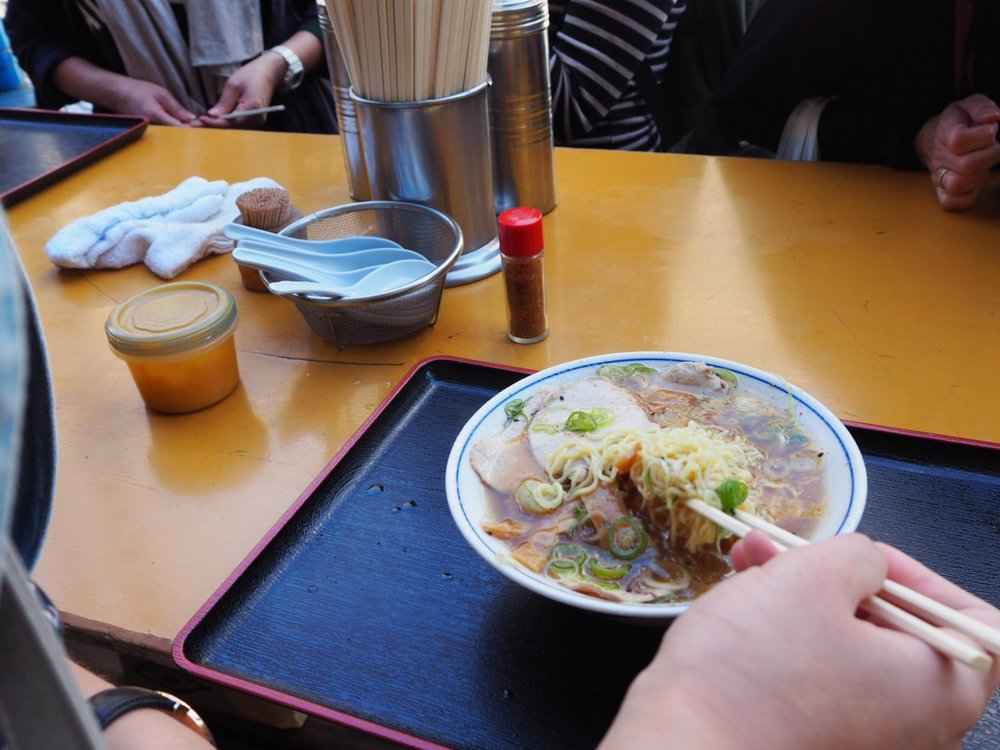 Sister's breakfast ramen on the crowded sidewalk in front of Tsukiji Fish Market
