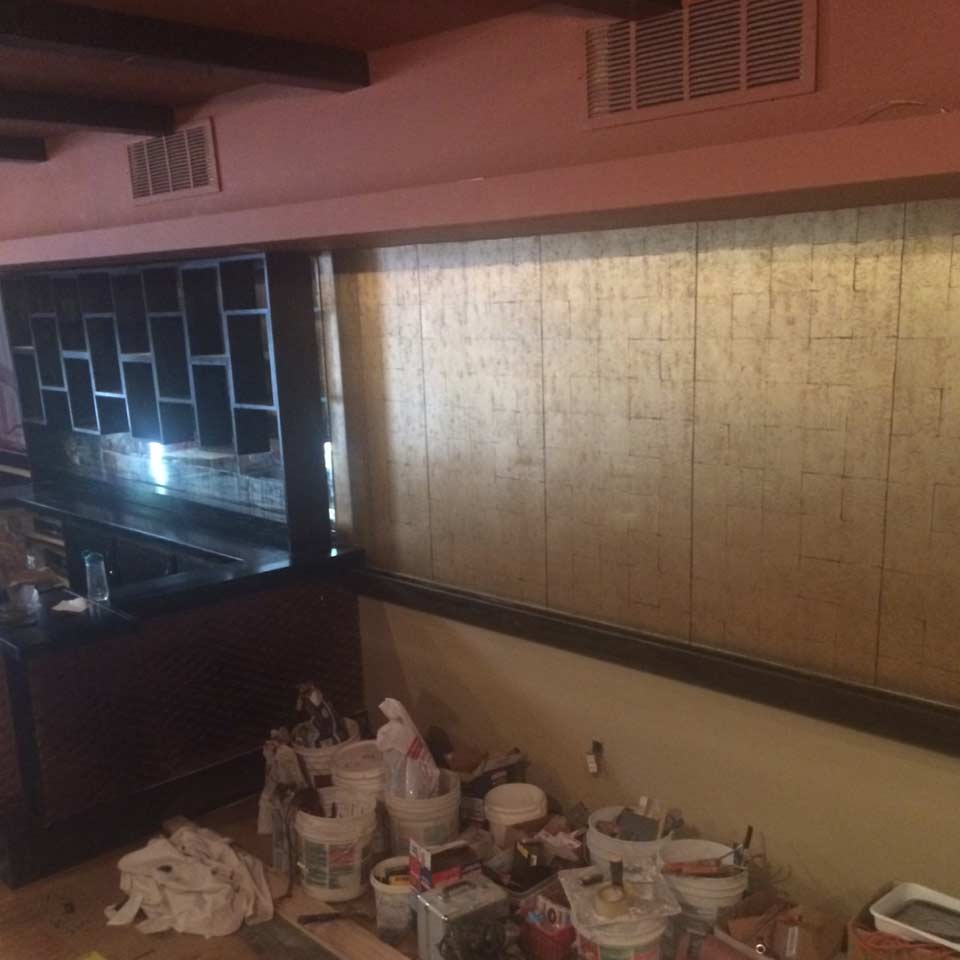 The bar shelving is painted black, the ceiling is painted a cozy brick color, and new gold wallpaper is up.