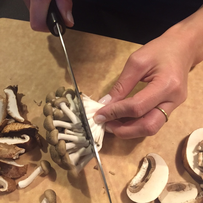 Slicing into brown clamshell mushrooms