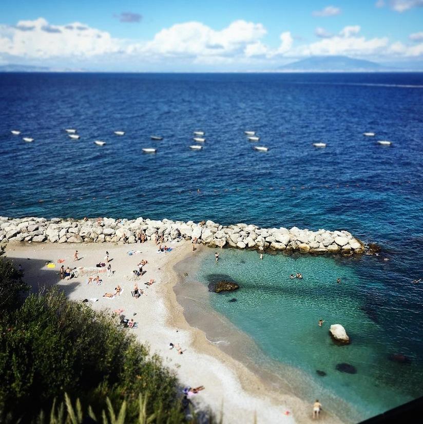 The beach in Capri. Image via   @lweatherbee  on Instagram.