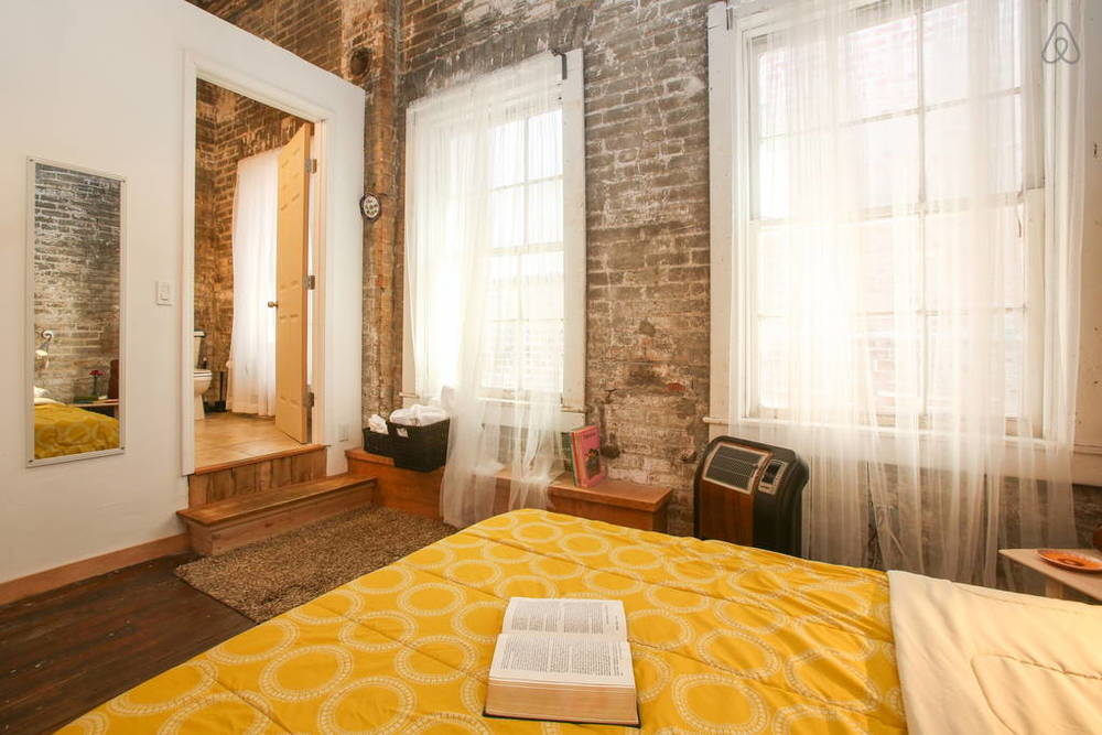The sunny bedroom has huge windows which brings in lots of amazing natural sunlight. I also love the old wood floors!  Image via   Airbnb