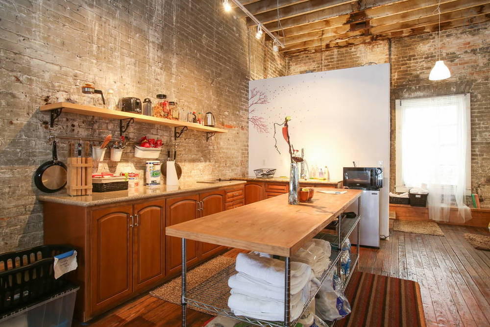 The kitchen has granite counter tops and a stainless steel sink.  Image via   Airbnb