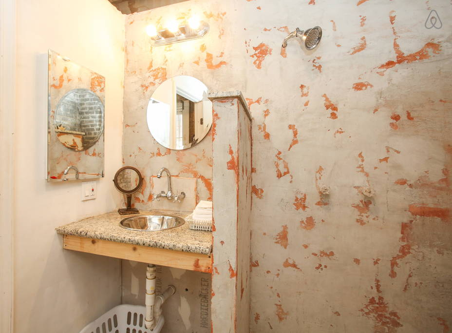 I love the funky industrial looking walls in the bathroom.  Image via   Airbnb