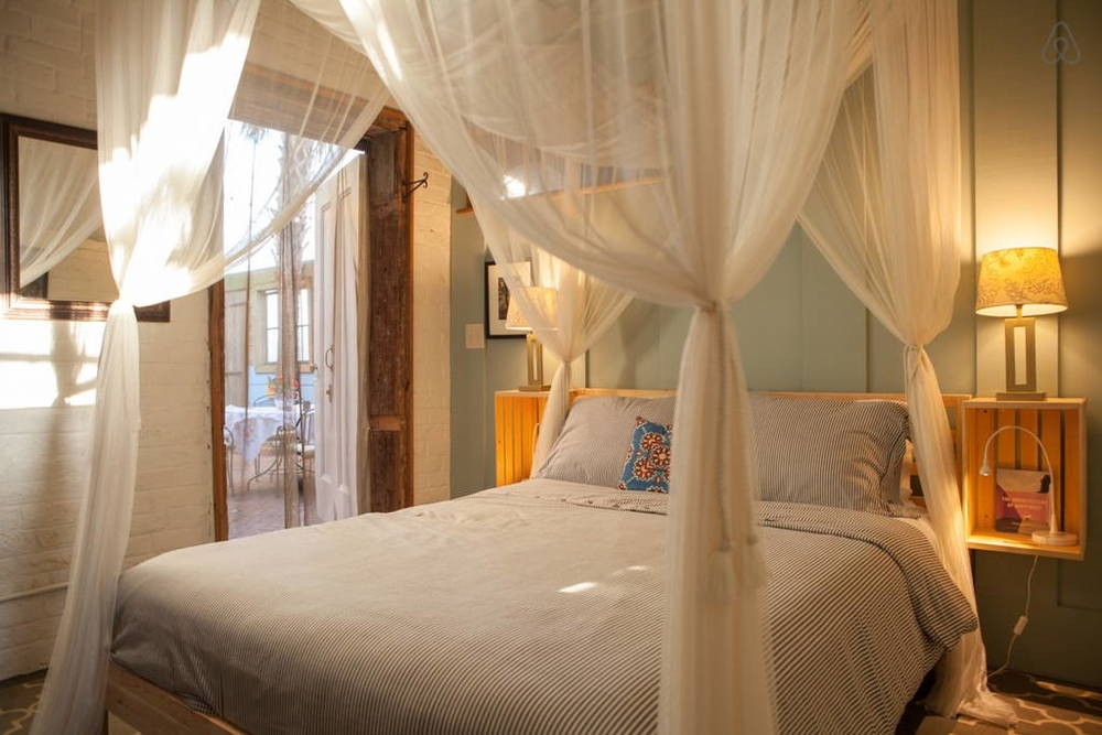 I love the canopy bed in this master bedroom.  Image via   Airbnb