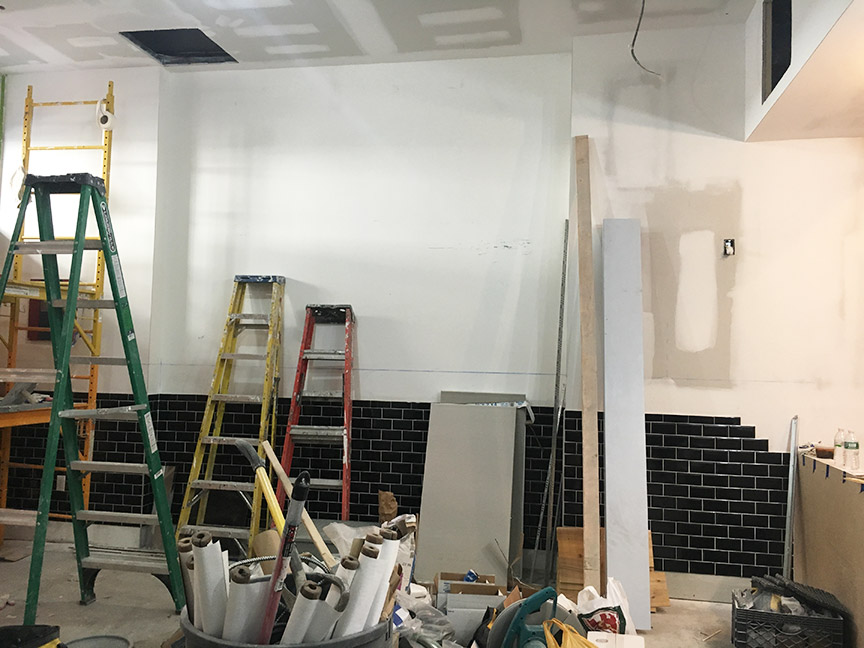 Changes are starting to happen, but the place is still a mess. We took down the unflattering fluorescent light fixtures and replaced them with energy-saving LED pendant and track lighting. The walls are being painted and the black subway tiles are going up. The space is looking better, but there is still a lot of construction debris everywhere.