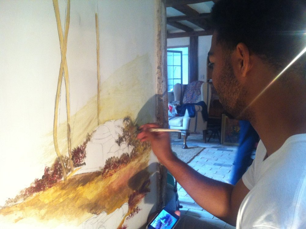 Jarrell painting a commissioned mural