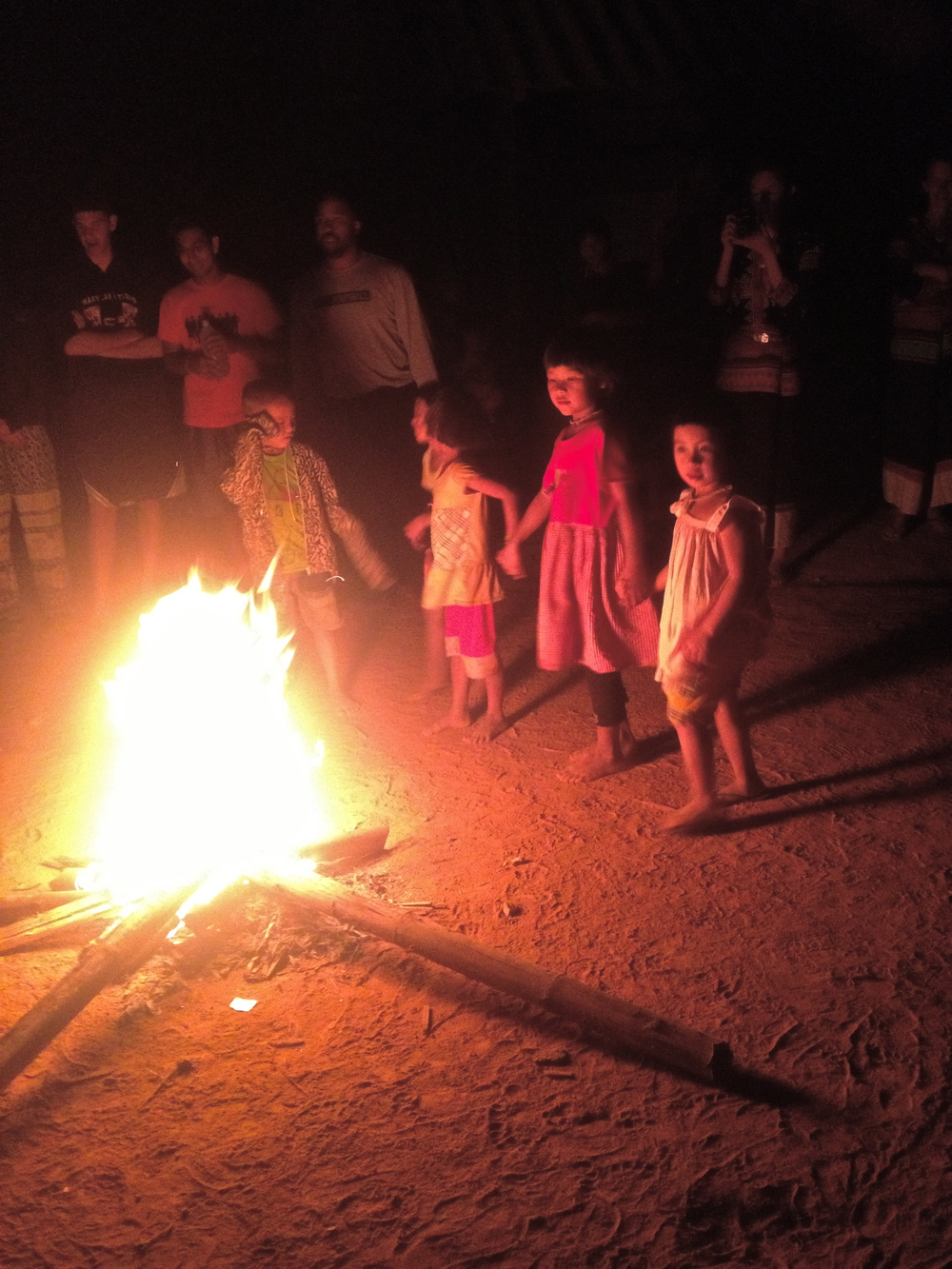 Village children dancing around bonfire