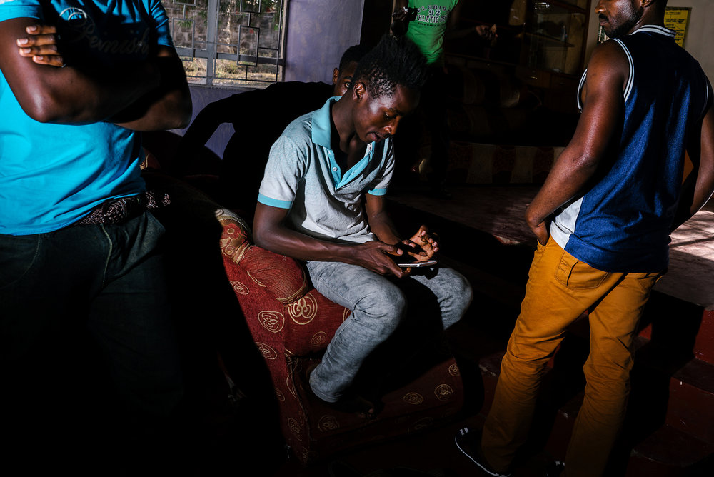 In a town outside of Nairobi, Kenya, a couple dozen LGBT refugees from Uganda lived together in a house, both for protection and for camaraderie. Here, a few at the house gather in the living room. After a few months, however, the house was evacuated and its residents scattered.