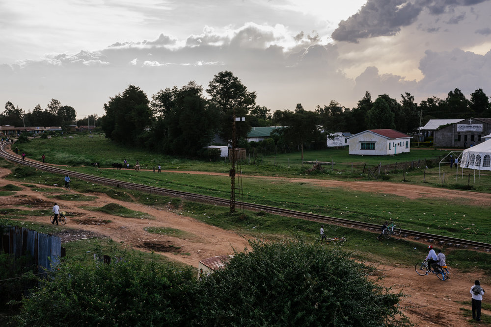 Residents of Bungoma, a city in western Kenya, walk along the railways in the evening.