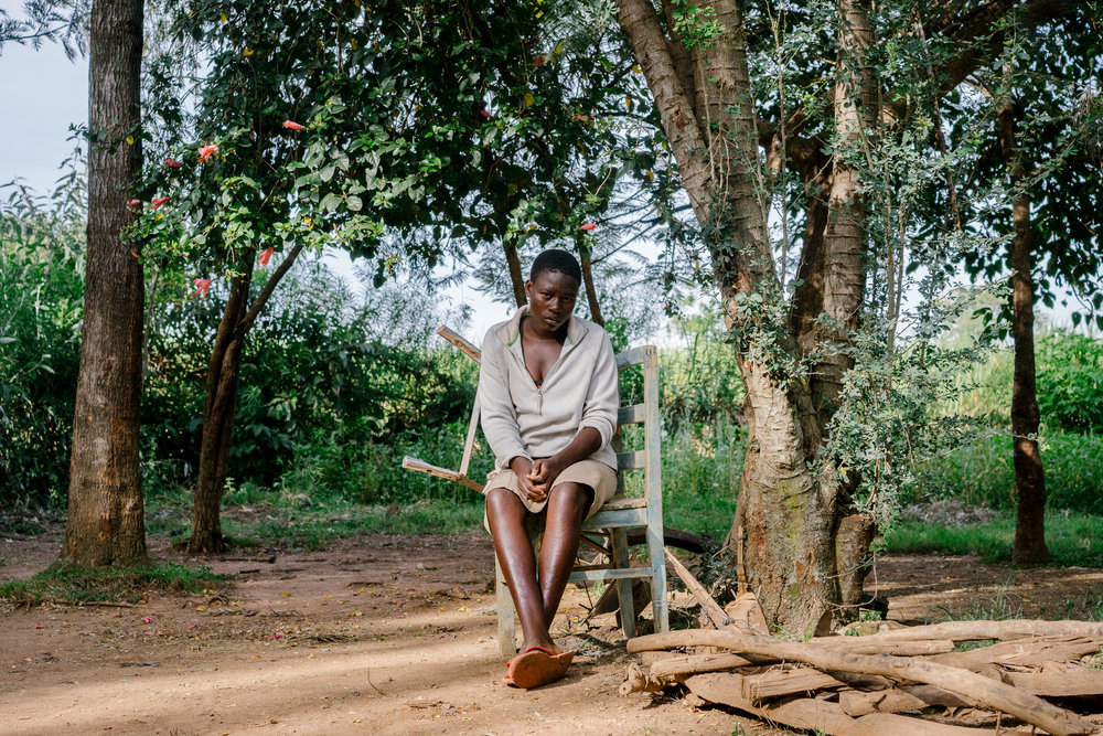 Consolata sits beneath a tree in front of her home.