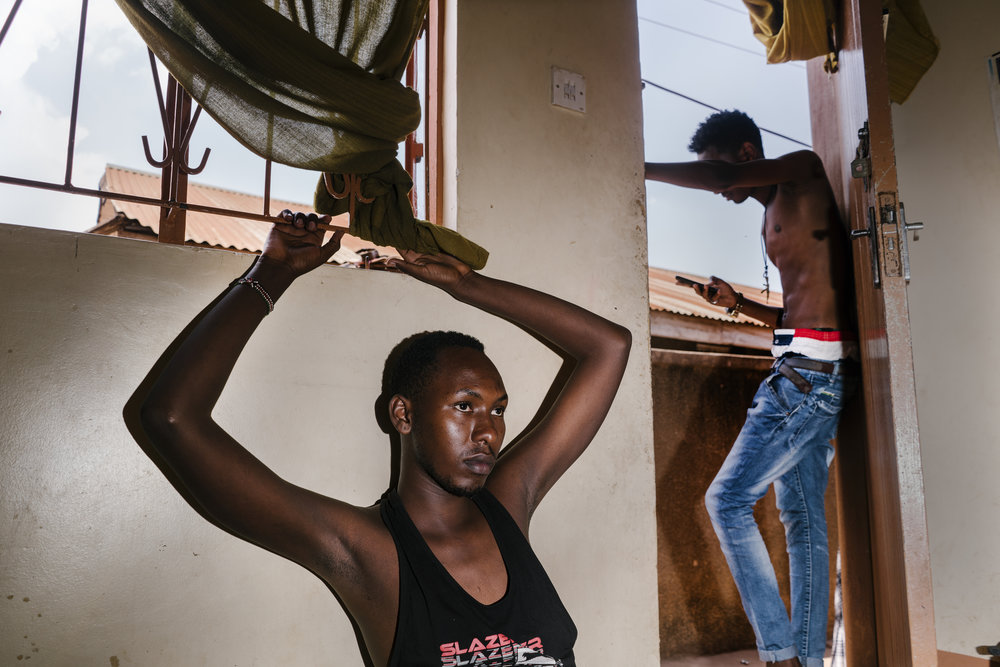 "Javan, a young transgender woman, sits in the family's living room, while her brother Shema, 18, who is bisexual, stands in the doorway. Javan spent six months in Kenya as a refugee there after a gang of men beat and stripped her naked near her home, and then forced to walk home naked while the mob chanted, ""She's a homo"" behind her. She returned to Uganda, but now faces frequent abuse from the general public."