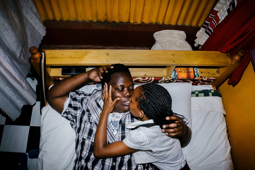 Cynthia is a lesbian activist and refugee from Burundi. She fled her country after authorities beat her and cut her with machetes for being gay. Here, she lays in bed with her Kenyan girlfriend in the apartment the two shared in Nairobi, Kenya. She has since been resettled in the United States.