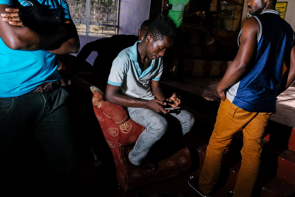 In a town outside of Nairobi, Kenya, a couple dozen LGBTQ refugees from Uganda lived together in a house, both for protection and for camaraderie. Here, a few at the house gather in the living room. After a few months, however, the house was evacuated and its residents scattered.