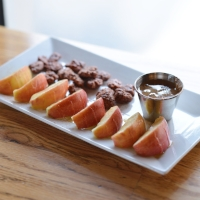 Honeycrisp Snack Plate  slices apples topped with honey & cinnamon, served with almond butter  and cinnamon pecans