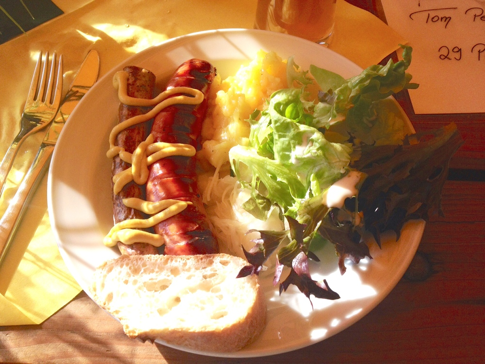 German grill food: Fränkische Bratwurst, Rote Wurst, German potato salad, sauerkraut, salad with yogurt dressing, and a slice of baguette