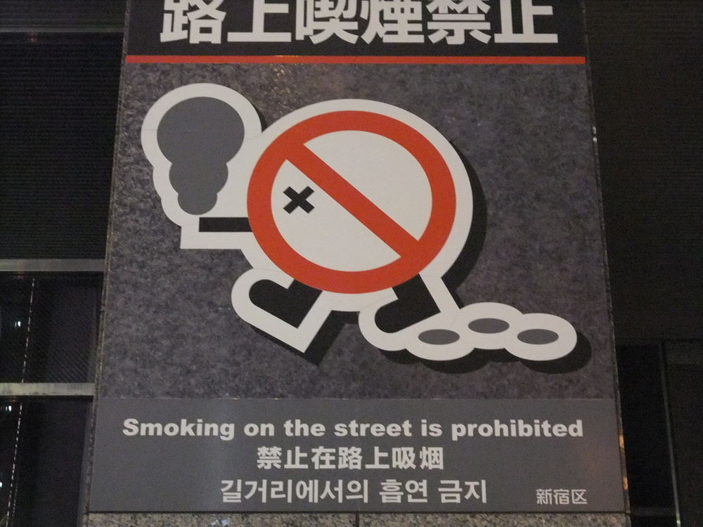 No smoking sign on a street, also conveniently in English