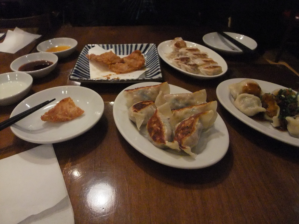 A traditional selection of pan-fried and steamed  gyoza  with fried pork skin on the top left plate