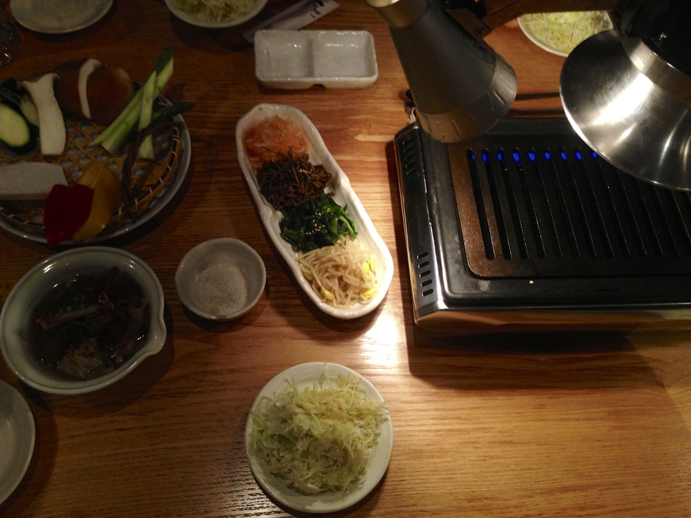 Yakiniku  table in Odaiba with vegetables, soup, dipping salt, cabbage salad, and different kinds of Japanese pickles