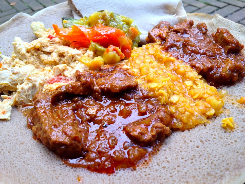 Meat tasting platter with chicken, beef, lamb, vegetables, and lentils on injera at Injeera