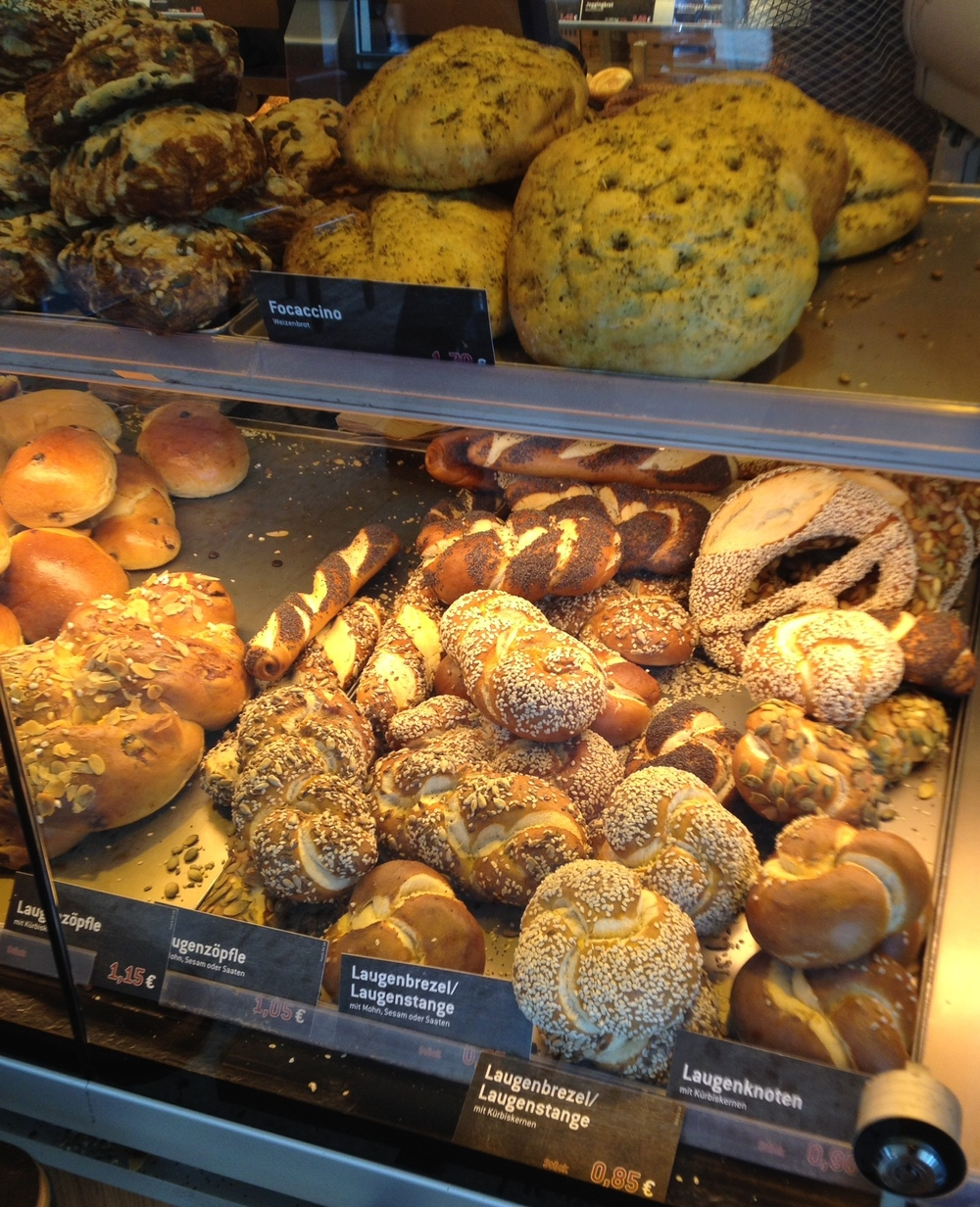 Rolls and loaves of bread for sale in a bakery window