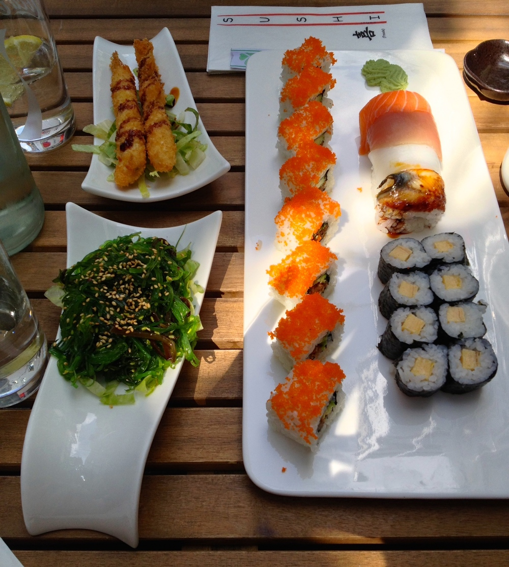 Clockwise from the top left: shrimp tempura, spicy tuna roll, rainbow roll, egg omelette roll, and seaweed salad
