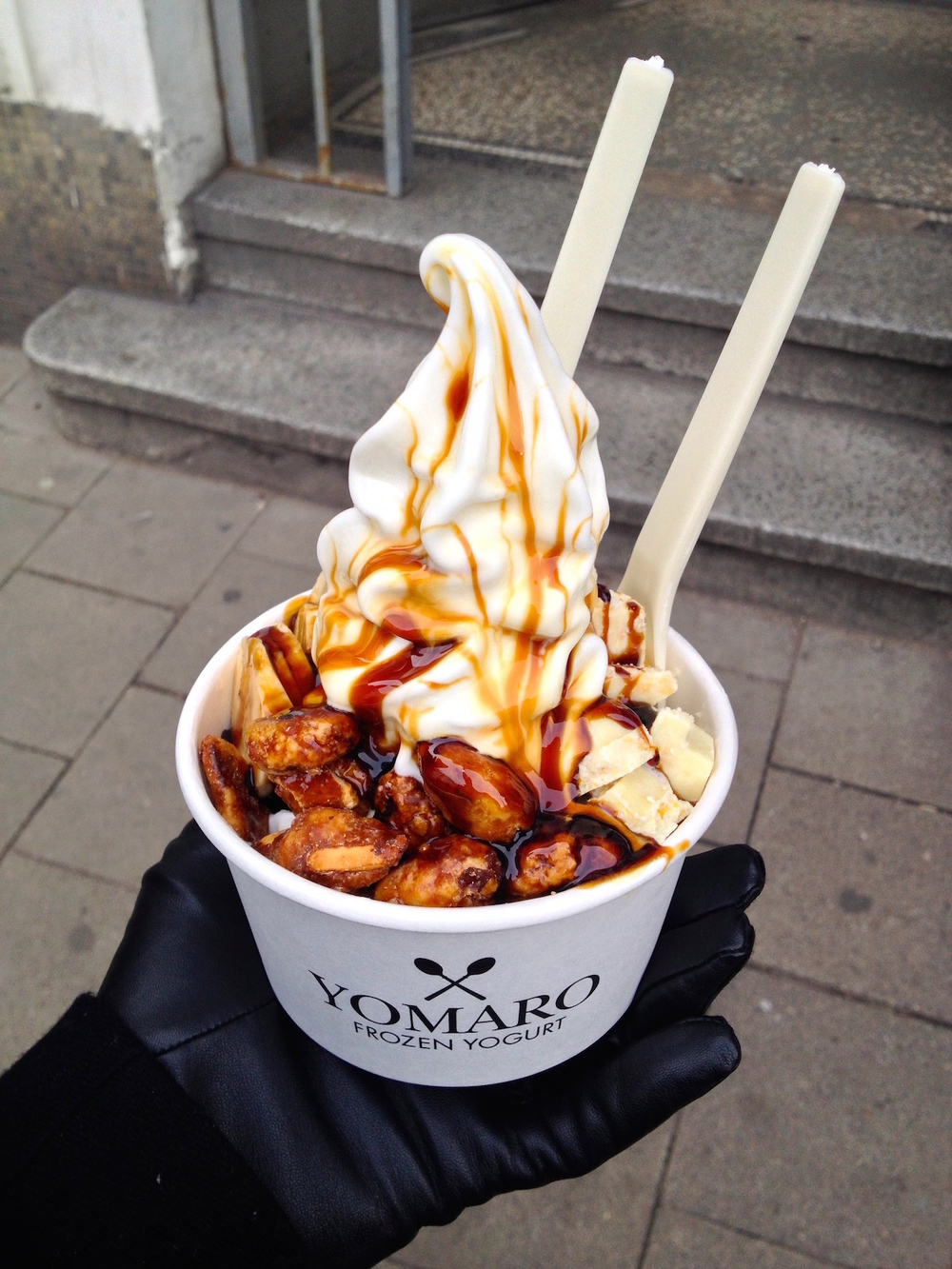 Medium frozen yogurt with white Ritter Sport coconut chips, banana slices, candied almonds, and caramel sauce