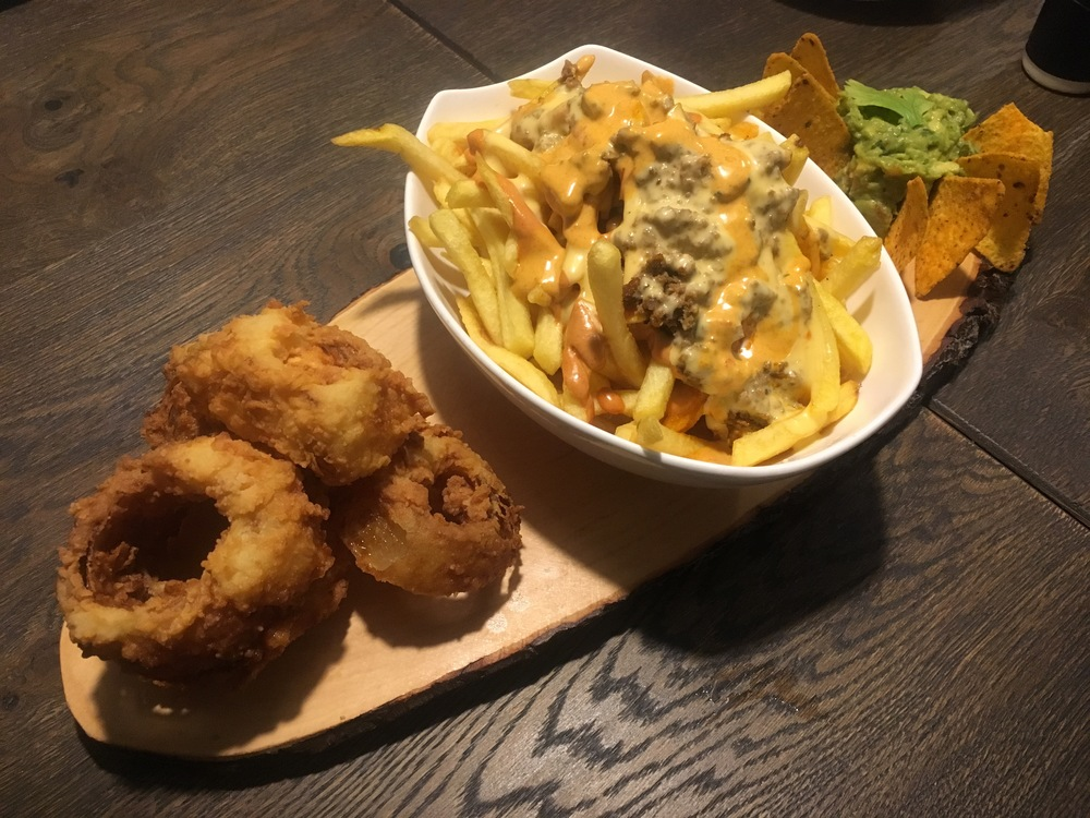 The appetizer platter with onion rings, chili cheese fries, and guacamole