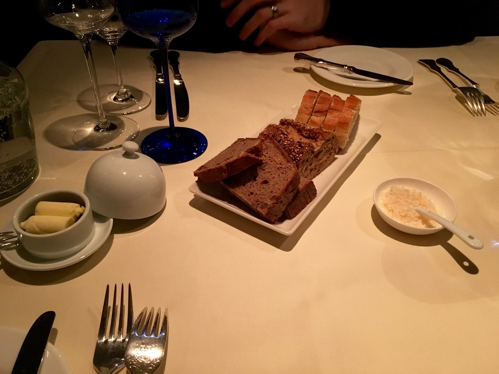 The table setting with bread, butter, and river salt